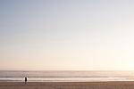 Woman walking along ocean beach alone in tranquil scene