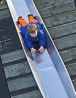 child playing on a sliding board