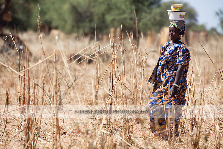 "In West Africa, certain villages have markets that ""assemble"" at regular intervals, such as weekly or every three days.  People from villages around the region come on market day to buy and sell food, livestock, and other goods and services.  Here, a woman carries goods on her head to the village market of Bourro in northern Burkina Faso."
