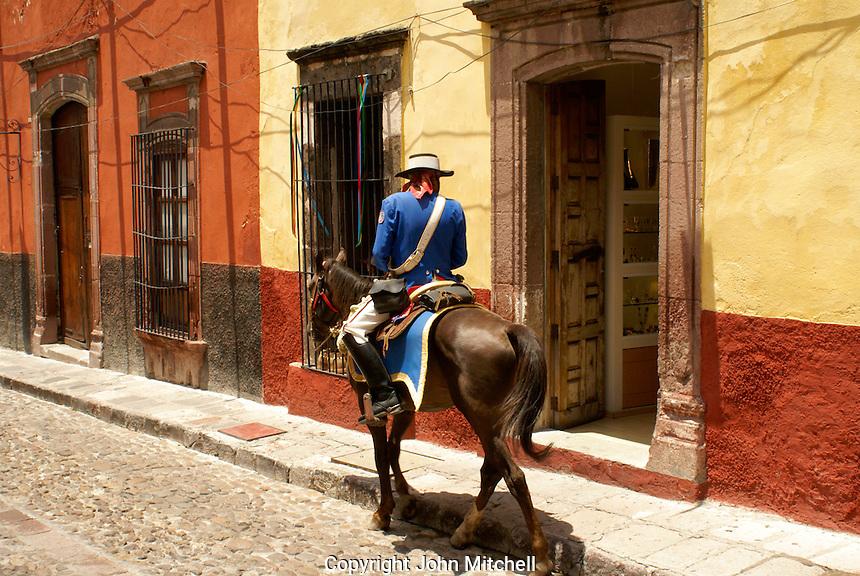 Spanish policeman on horseback patrolling street in San Miguel de Allende, Mexico. San Miguel de Allende is a UNESCO World Heritage Site.
