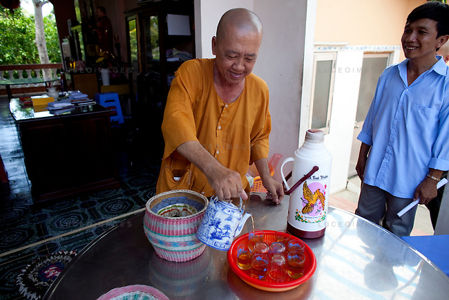 Thich Thien Tri, a monk at the Long Co Tu pagoda, pours tea made with clean water provided by the Tien Phat enterprise in the Luong Hoa Lac commune. Tien Phat owner Nguyen Van Khang, 40, at right.