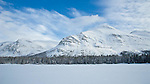 snow covered boat house on two medicine lake, glacier national park,