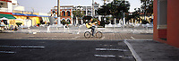 A cyclist rides by the Plaza clutching his guitar in Tlacotalpan Veracruz, 2002. The colonial port of Tlacotalpan is one of the best preserved small cities in mexico, it was declared a World Heritage town.  It is also the epicenter of the Cuban-Spanish influenced  Son Jarocho music.