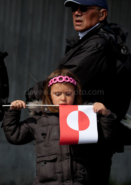 Little girl holding Greenland flag, National Day, celebrating Self-government, Nuuk, Greenland.. From June 21 2009, Greenland moves from being under 'home rule' to 'self-governance' in a ceremony attended by the Danish Royal family and other heads of state.