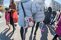 Woman with a Hello Kitty handbag on Eighth Avenue in the Sunset Park neighborhood in Brooklyn in New York on Sunday, February 28, 2016 during the Lantern Festival street fair. Sunset Park has become Brooklyn's Chinatown as Chinese and other Asian groups have moved there and businesses have sprouted up to cater to them. (© Richard B. Levine)