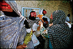 Women take a break after shopping at the weekly open-air market. Masks in this region are said to be part of local  pre-Islamic traditions, although these women are Muslim.  Minab, Iran. November 1998