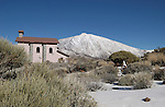 Small chapel below snow capped Mount Teide with plants and grasses in the foreground, Tenerife, Canary Islands.