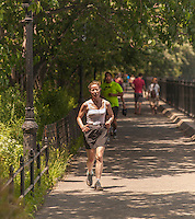 Exercise enthusiasts run along the reservoir in Central Park in New York on Sunday, July 7, 2013. Despite temperatures in the nineties with corresponding humidity causing the heat indices to hit 105, people participated in some of their favorite exercises. Sunday is expected to be the hottest day of the heat wave with the city issuing a heat advisory until 8 PM. (© Richard B. Levine)