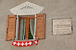 Window with Swiss flags on a house that dates back to 1597 in Bondo, a Swiss Bregaglia Valley town; The decorations on the house are patterns scratched out of the still wet wall, decorative artwork called sgraffiti, traditionally done in two colors and originating in Italy, brought to the Engadin region of Switzerland in the 16th century and is still used today;