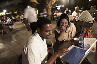 Lo'ay Ahmad (left) and Hind Ibrahim relaxing at Ozone, Khartoum's premier outdoor cafe, complete with Wi-Fi access and water vapour air conditioning, pictured in Khartoum, Sudan, on Friday, Apr. 13, 2007..Khartoum is modeling itself as the Dubai of Africa and despite Western sanctions the city is booming. Away from the troubles and poverty that plaque the rest of Sudan, development in Khartoum is moving at an astonishing rate. Investment from the East, and in particular China, allowed the Sudanese economy to grow by 11% in 2007. This growth is driven largely by oil, with production rising from 63,000 barrels per day in 1999 to over 500,000 barrels today.