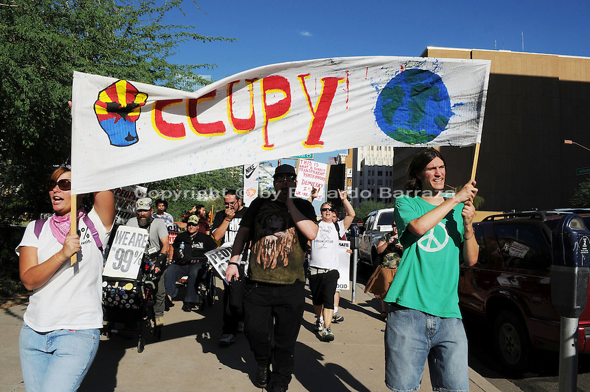 """Phoenix, Arizona. September 17, 2012 - A small crowd of demonstrators in Phoenix, Arizona gathered to mark one year since the beginning of the Occupy Movement that opposes Wall Street and large corporations that represent the one percent who control wealth in the United States. In this photograph, Occupy Phoenix activists Rachel Skaggs (left) and Michael Nehl Royeran (right) hold an """"Occupy"""" banner as they lead the march on Jefferson Street in Downtown Phoenix. Activists marked the first anniversary of the Occupy Wall Street Movement. Photo by Eduardo Barraza © 2012"""