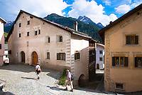 Tourists stroll in the Engadine Valley in village of Ardez with painted stone 17th Century restored houses, Switzerland