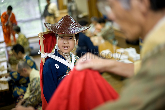 """Leo Shigeta, 16, is given a helping hand by Akimasa Matsumoto to put on traditional attire prior to the """"yabusame-shinji"""" horseback archery ritual on the final day of the Reitaisai grand festival at Tsurugaoka Hachimangu shrine in Kamakura, Japan on  14 Sept. 2012. The yabusame ritual is performed by members of the Ogasawara school, which began mounted archery rituals in the 12th century. .Yabusame was originated in middle of 6th century as a Shinto ritual. Today there are various styles and manners of Yabusame inherited by different shrines and particular families. It was common in the ancient past that the result of Yabusame depended on the number of targets successfully hit, and also fragments of the target were used to tell fortunes. The target and arrows used in successful shots were kept as amulets. The initiation of Yabusame in Tsurugaoka Hachimangu was 1186. Photographer: Robert Gilhooly"""