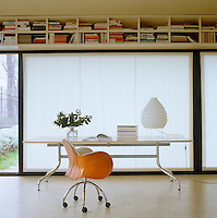 A table and saddle-like leather swivel chair, both by Vico Magistretti, have been placed beneath a horizontal bookcase which is suspended from the ceiling