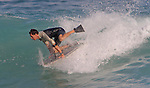 A boarder at Sandy Beach in Hawaii stands up on his board and gets a good ride.