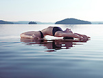 Young woman practicing sunrise yoga on a platform in calm water on the lake during misty morning. Yoga Fish posture, Matsyasana. Muskoka, Ontario, Canada.