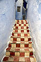 Checkered red and white steps in blue in the medina in Chaouen, Morocco.
