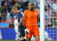 A dejected USA goalkeeper Tim Howard walks past team-mate Jay DeMerit