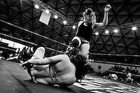 """A female Lucha libre wrestler Keira kicks down her rival Sexy Polvora during a fight at Arena Plan Sexenal in Mexico City, Mexico, 29 May 2011. Lucha libre, literally """"free fight"""" in Spanish, is a unique Mexican sporting event and cultural phenomenon. Based on aerial acrobatics, rapid holds and the use of mysterious masks, Lucha libre features the wrestlers as fictional characters (Good vs. Evil). Women wrestlers, known as luchadoras, often wear bright shiny leotards, black pantyhose or other provocative costumes. Given the popularity of Lucha libre in Mexico, many wrestlers have reached the cult status, showing up in movies or TV shows. However, almost all female fighters are amateur part-time wrestlers or housewives. Passing through the dirty remote areas in the peripheries, listening to the obscene screams from the mainly male audience, these no-name luchadoras fight straight on the street and charge about 10 US dollars for a show. Still, most of the young luchadoras train hard and wrestle virtually anywhere dreaming to escape from the poverty and to become a star worshipped by the modern Mexican society."""