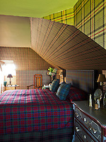 An attic bedroom is decorated in tartan with wallpaper by Ralph Lauren