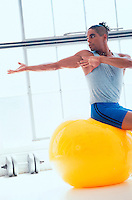Man using a therapy ball during his workout.