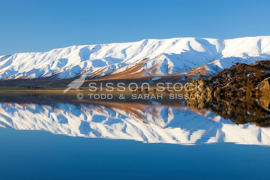 Snow covered Hawdun Ranges reflection in Falls Dam, near St Bathans, Central Otago, New Zealand