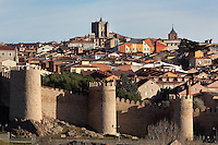 City Walls, 11th-14th century, Avila, Spain, with Cathedral, 11th-15th century, in the distance (looking West). Avila has superbly preserved walls built as fortifications against the Moors, an ancient cathedral, Romanesque churches, and is a pilgrimage destination due to its association with Carmelite nun St Teresa (1515-82), canonized 1622. The Old Town has been designated a UNESCO World Heritage Site. Photograph by Manuel Cohen.