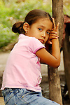 A girl in Pico Bonito National Park, Honduras, rests her head on her folded hands on a wood pole.