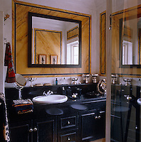 A collection of silver trophies are on display in this very masculine black and yellow bathroom