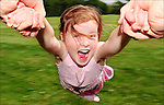 A young girl being swung around by her arms