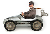 Mn in a wind-up/pedal car on white background