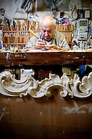 Artisan wood carver and furniture restorer, Luigi Mecocci, working in his bottega on Via dei Velluti, Florence, Italy