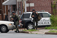 SWAT team officers patrols outside a house where an armed man with multiple hostages is barricaded in a standoff that began Friday afternoon. Trenton New Jersey, May 11, 2013. by Kena Betancur / VIEWpress
