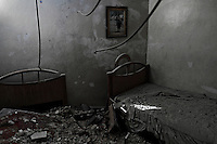 The room where two children used to sleep is now empty after a mortar shell tore through the roof of a civilian home in the Salahadeen neighborhood of Aleppo.<br />