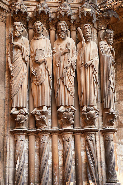 South Porch right jam. Cathedral of Chartres, France. Gothic statue of the Apostles (haloed, carrying the instruments of their deaths). From left to right they are Paul (characteristic facial features, carrying a sword) , John (beardless, carrying a book and what Houvet says is part of a palm frond) , James Major (carrying a sword and a pilgrim's pouch) , James Minor (carrying a club) , Bartholomew. On the socles on which they stand are their persecutors, mostly crowned figures holding scrolls and looking upward. A UNESCO World Heritage Site.