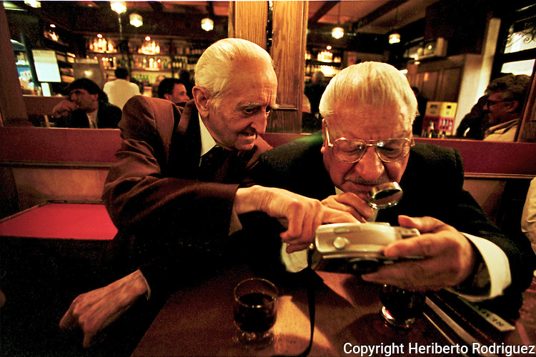 Two elderly Chileans look at their photograph on the display of a digital camera in a old-fashion bar in Santiago de Chile, April 20, 1998.
