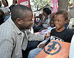 Ezekiel Batista, a missionary in Haiti from the Cuban Council of Churches, a member of the ACT Alliance, delivers a blanket and hygiene kit to a disabled boy who survived Haiti's January 12 earthquake. He is part of a group of disabled Haitians who are receiving special attention from ACT Alliance members. Batista is program manager for a program focusing on the needs of Haiti's disabled, sponsored jointly by the Cuban Council of Churches and Church World Service Haiti.