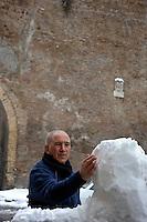 Nevicata a Roma.Snowfall in Rome.Uomo mentre prepara un pupazzo di neve.Man prepares a snowman...