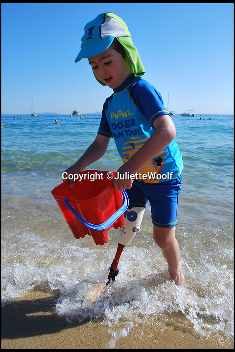 BNPS.co.uk (01202 558833)<br /> Pic: JulietteWoolf/BNPS<br /> <br /> ***Please Use Full Byline***<br /> <br /> Rio on his recent holiday to France being able to fill his bucket by himself for the first time. <br /> <br /> <br /> This is the heartwarming moment a disabled boy was able to swim with a prosthetic leg for the first time.<br /> <br /> Rio Woolf, aged six, had his lower right leg amputated when he was 14-months-old after being born without a tibia, knee, or ankle joint.<br /> <br /> The plucky youngster learnt to walk with NHS limbs and now uses a carbon blade, but has been removing it for swimming.<br /> <br /> He normally take it off in the changing rooms and gets carried to the pool or uses a wheelchair.<br /> <br /> But Rio has now received a state-of-the-art waterproof limb that means he can jump into the water like any other child his age.<br /> <br /> The prosthesis has also improved his lower body balance which has made his back stroke much faster.<br /> <br /> He has also worn it on holiday to France with his mum Juliette and dad Trevor, both 48, and enjoyed going on the beach and in the sea.<br /> <br /> The new leg was created by a leading prosthetics clinic who used an Ossur Junior Vari Flex-Foot with it, so Rio can also wear a shoe.<br /> <br /> It cost around 5,000 pounds and will need to be replaced as Rio grows.