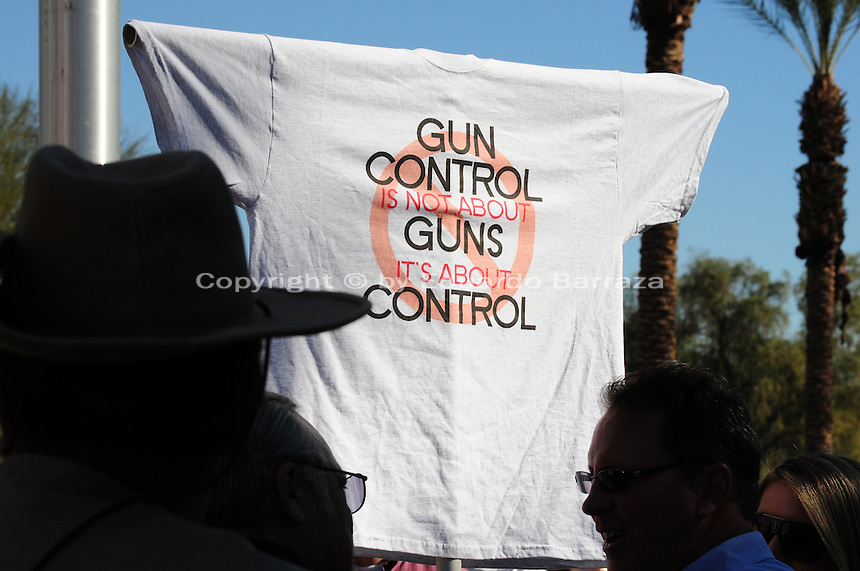 """Phoenix, Arizona. January 19, 2013 - Demonstrators in Phoenix display a T-shirt expressing their views on gun control in America. As President Barack Obama proposed new gun regulations last week, gun owners demonstrated against it with national """"Guns Across America"""" rallies to defend the Second Amendment. Dozens showed up at the Arizona State Capitol, many of them carrying weapons. Photo by Eduardo Barraza © 2013"""