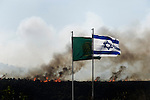 ISRAEL, Carmel Forest : An Israeli flag flutters near flames in the Carmel Forest on the outskirts of Haifa on December 3, 2010 as thousands of Israeli firemen and rescuers fight to control the massive forest fire that has already killed 41, as global help poured in to battle the biggest inferno in the country's history.© ALESSIO ROMENZI