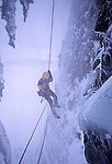 American female mountainaeer Kitty Calhoun rappels from the top of a frozen waterfall in stormy winter conditions near Merkigil Iceland.