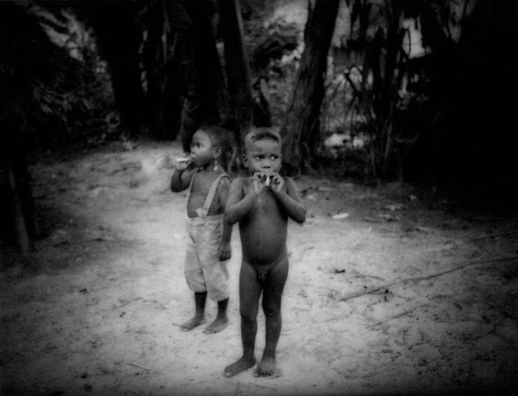 Batek Negrito children smoke clove cigarettes, Taman.Negara Rainforest, Malaysia.  Several hundred Batek Negritos have sought refuge within this national park from the adjacent logged-over forests because hunting there is no longer productive.  This has not insulated the Batek from vices of the outside world.  The gov't wishes and has failed to assimilate all Batek into mainstream Malaysian society.  These undersized (pygmy) people are the original inhabitants of the Malay Peninsula and directly related to the Negrito peoples of the Philippines.