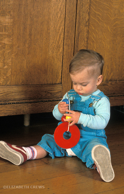Berkeley CA Boy eleven months old studying toy, coordinating toy and hands
