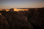 The sun sets over Bighorn canyon as seen from the Devil's Lookout.  The canyon is located just east of Lovell, Wyoming, and is a spectacular sight that somehow doesn't get as much glory as it deserves. The area was originally impassable by human travelers. About 10,000 years ago indigenous hunter-gatherers created the Bad Pass Trail above the canyon's western rim. This same trail was later used by fur trappers who traveled around the area.. The canyon was carved out by the Bighorn River eons and eons ago. Over time, the moving river left a 2,200 foot deep canyon in the desert country. In 1967 the Yellowtail Dam was built and backed the canyon water up, thus filling the canyon with water. The dam provides 250,000 watts of energy for the western United States. .