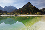 Julian Alps, Peaks of Prisojnik and Razor reflected in pools beside the Velika Pisnca river in autumn.