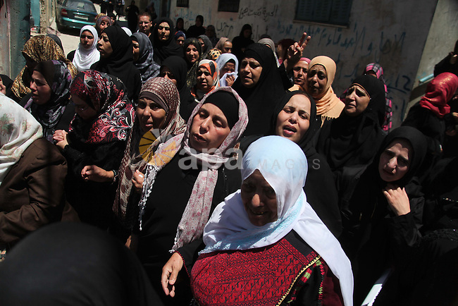 Palestinian women grieve over the body of Eid Fadhelat, 32, who was injured during clashes with Israeli soldiers Friday, during his funeral at Al-Arrub refugee camp near Hebron city in the West Bank on Saturday, July 26, 2014. Eid Fadhelat was shot during clashes that started late Friday with Israeli troops at the refugee camp and died later. In the West Bank, which had been relatively calm for years, protests raged Friday against Israel's Gaza operation and the rising casualty toll there. Photo by Mamoun Wazwaz