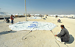 Workers erect new tents in the Zaatari Refugee Camp, located near Mafraq, Jordan. Opened in July, 2012, the camp holds upwards of 50,000 refugees from the civil war inside Syria. A dramatic rise in the camp population is expected soon. International Orthodox Christian Charities and other members of the ACT Alliance are active in the camp providing essential items and services.