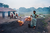 A woman stands next to the pile of coking coal in Bokapahari village in Jharia, outside of Dhanbad in Jharkhand, India.  Photo: Sanjit Das/Panos