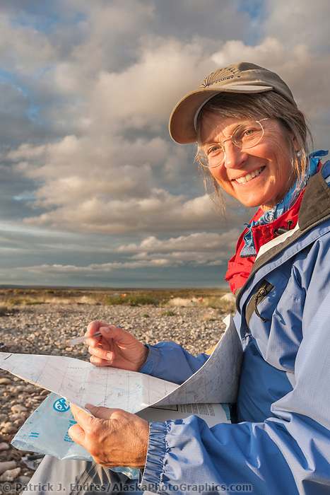 Debbie Miller checks locations on a topo map along the Etivluk river in Alaska's arctic National Petroleum Reserve Alaska.
